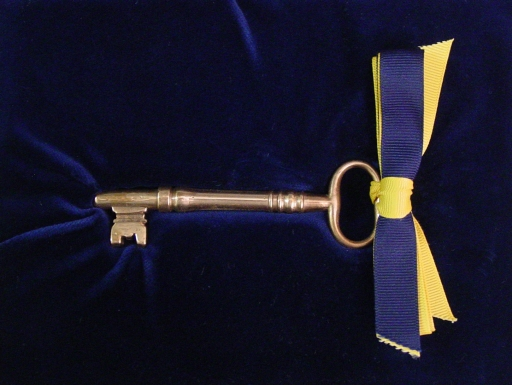 Key with blue and yellow ribbon.