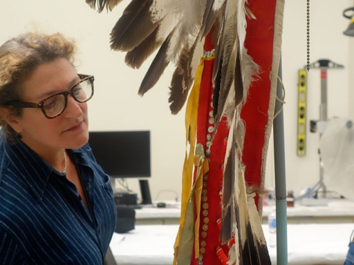 Conservator looking at headdress.