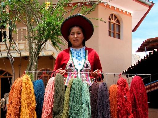 Peruvian woman holding colorful yarns.