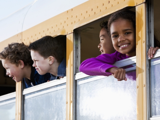 Smiling students in a school bus.