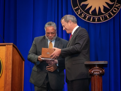 Chief Justice John Roberts presents Secretary Lonnie Bunch with the ceremonial key to the Smithsonian Castle.