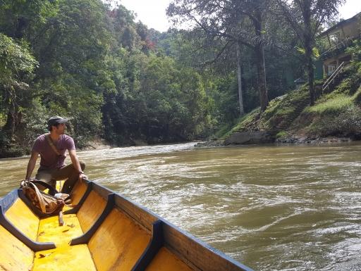 Man in stern of canoe as it goes down a river