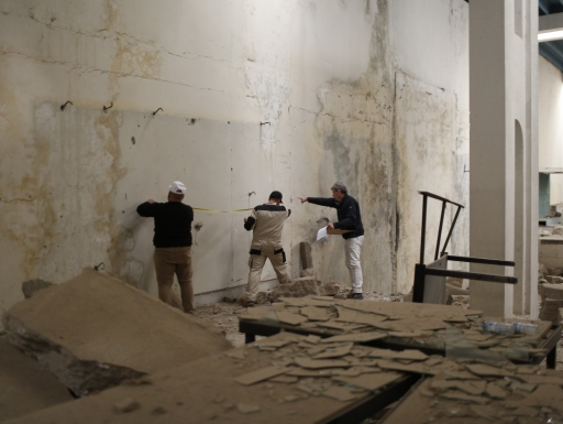 Three people work on a dilapidated building interior