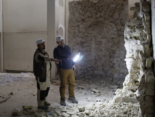 Two men stare at a crumbling wall