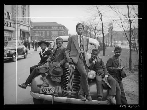 Dressed up Black boys sitting on hood of car