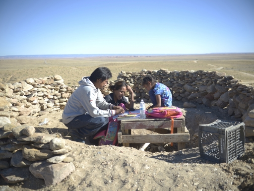 Three people sit in a makeshift classroom outdoors.