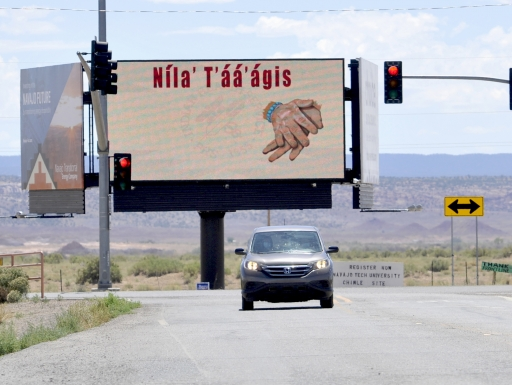 Car drives in front of billboard