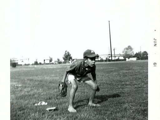 Young boy crouches in a field of grass with a baseball mitt in hand