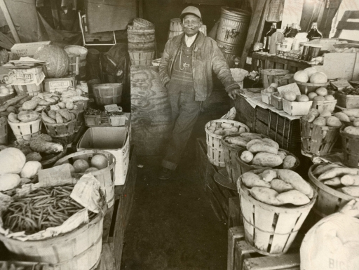 Man stands amid fruit and vegetable baskets