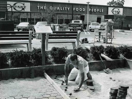 Man repairing road in front of supermarket