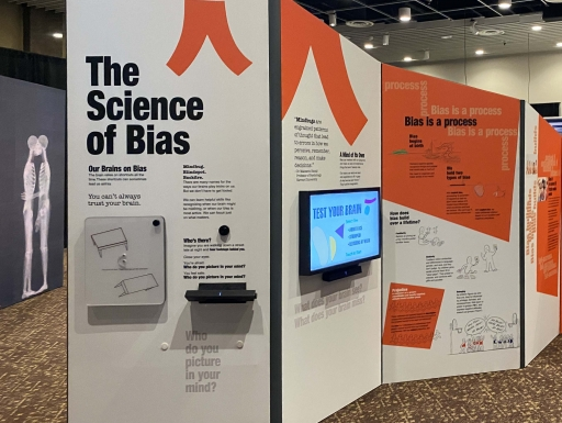 "Museum display of ""The Science of Bias"" with wall text and TV screens"