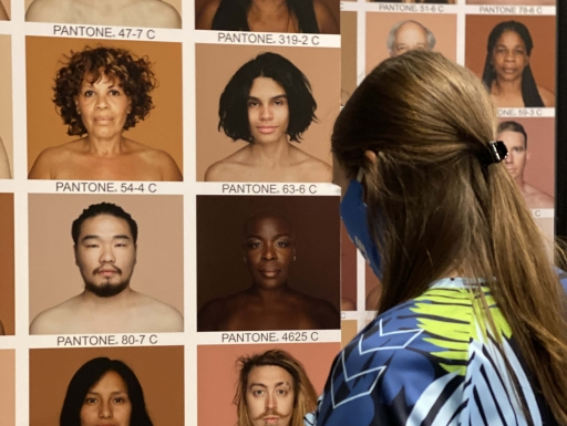Woman wearing mask looks at wall of portrait photography