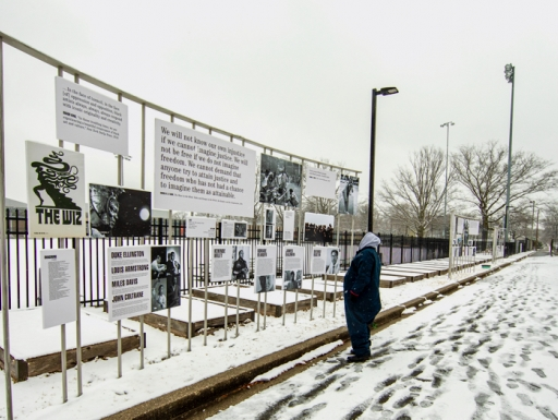 Person stands in snow looking up at art attached to a fence
