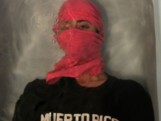 Red masked man wearing black shirt saying Muerto Rico