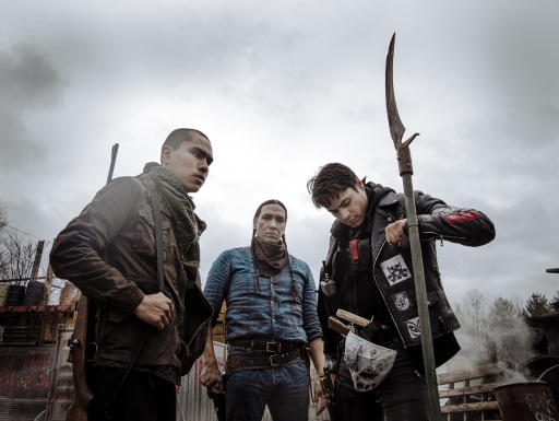 Three armed Native men, one staring into camera