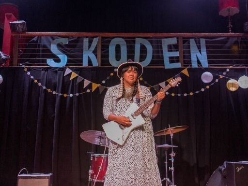 "Female guitarist on stage, ""Skoden"" banner in background"