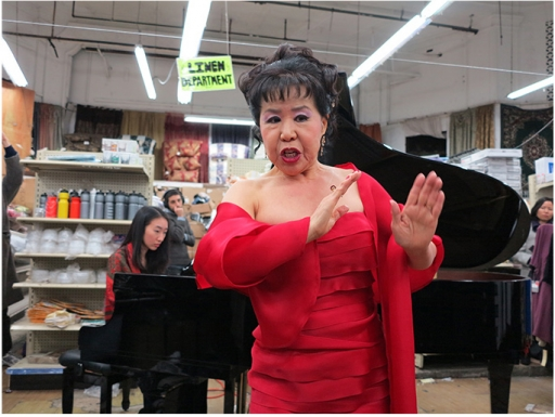 Asian woman in red dress in front of grand piano