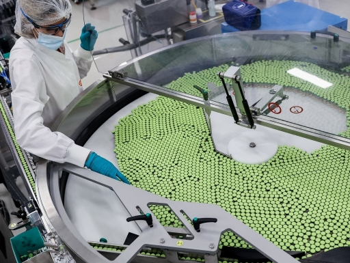 An employee is at work on the vaccine packing line of the factory of British pharmaceutical company GlaxoSmithKline