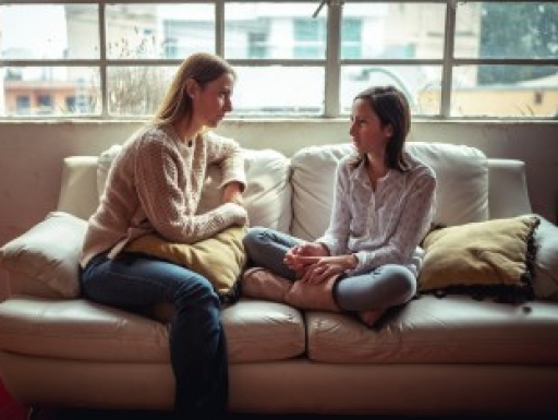 mother talking to daughter on a couch