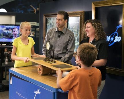 Children posing with pendulum model