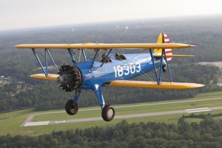 Blue and yellow biplane in flight