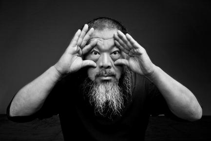 Black and white portrait of artist peering through his hands