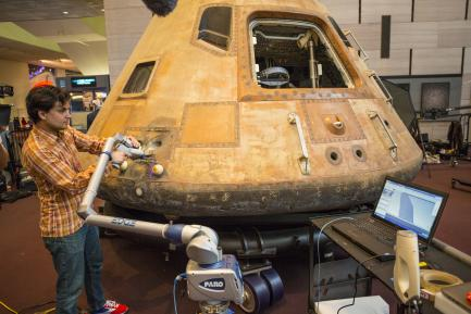 technician using laser to scan command module