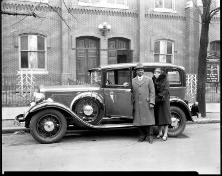 Couple stands next to old sedan