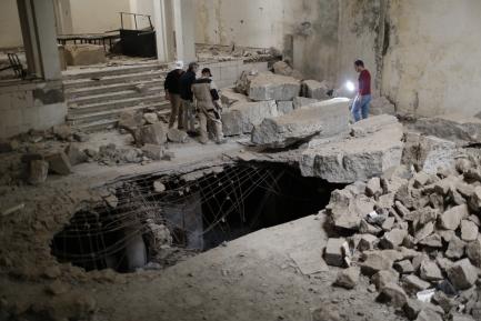 Three people survey large debri inside a building