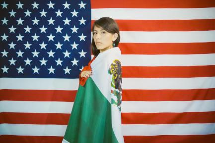 Woman wrapped in Mexican flag stands in front of American flag