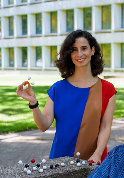 Woman holds a molecular model while standing outside