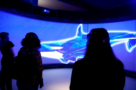 People watch video screen displaying an orca illustration