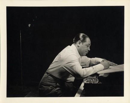 Duke Ellington in profile leaning over an open piano