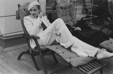 Marlene Dietrich dressed in white lounging on deck chair