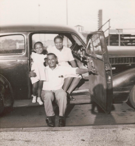 Mother, father, and daughter sit in open passenger seat of a car