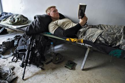 soldier reading while lying on cot