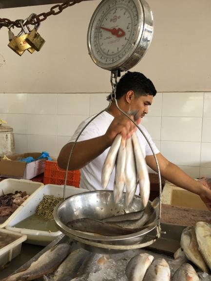 A fishmonger weighing fish