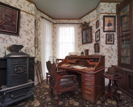 Room with desk and cast iron stovr