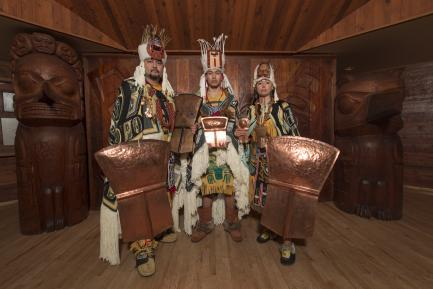 Costumed dancers carrying shields