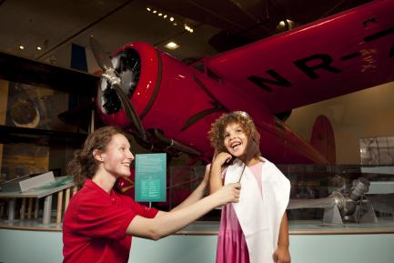 Museum Explainer Rose Agger helps a young girl dress up like a historic aviator