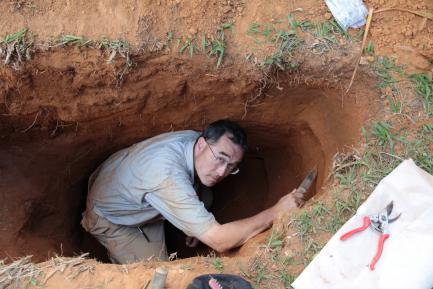 man digging deep into dirt