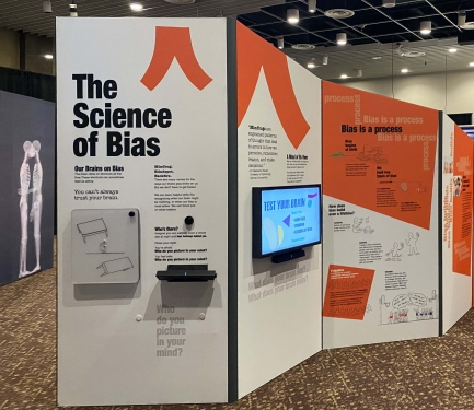 """Museum display of """"The Science of Bias"""" with wall text and TV screens"""
