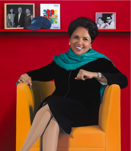 Indra Nooyi by Jon R. Friedman sitting in an orange chair with a red wall behind her.