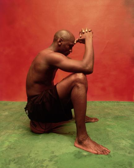 Black man sitting against red wall on green floor