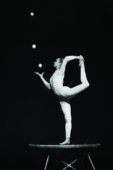 Black and white photo of woman in yog pose juggling