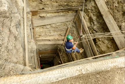 researcher descending into excavation