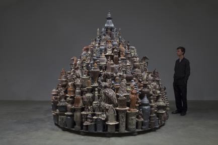 Artist standing next to his work, a sculpture comprised of china dishes