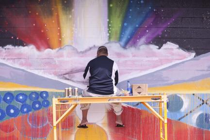 Still image from film Mele Murals showing artist working on rainbow mural