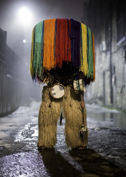 Person standing on city street completely obscured by colorful native costume