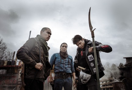 Three armed Native American men, one staring into camera